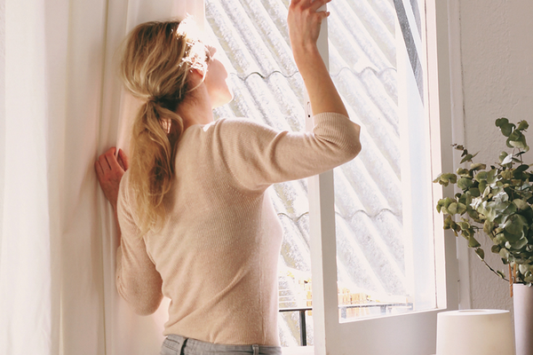 Woman opening up window to let fresh air into home with plant and air purifier for detoxing