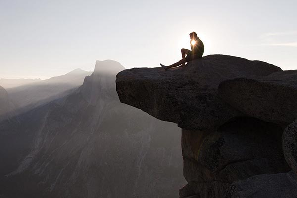Silhouette of man sitting near the edge of a rock cliff overlooking a view at sunrise