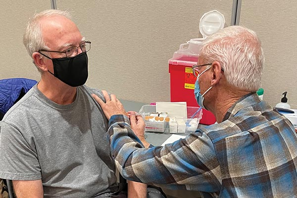 Older man receives COVID-19 vaccine from older male nurse.