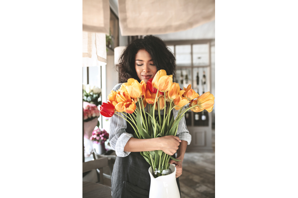 portrait of lady with dark curly hair holding a white vase with orange and red tulips