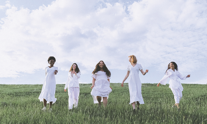 Group of naturally healthy women wearing white walking in a grassy outdoor space