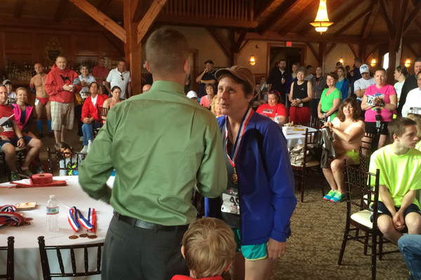 Age group winner Linda Corriveau is congratulated by Nick Pearson at the Tewksbury Memorial Day 5K Fun Run.