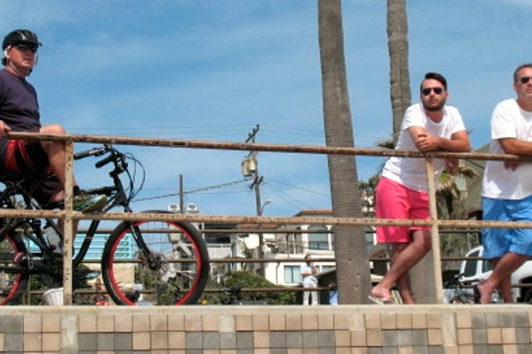 Beach-goers watch from the bike path area above the sand.