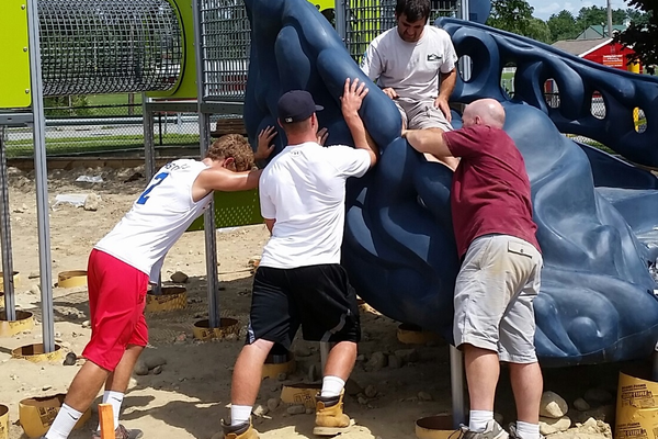 Tewksbury High School Football Team members help with the assembly one of the new climbing structures during the Funway Park Community Build Day. Photo by Paige Impink.