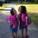 Samantha Holbrook, left, a first grader at Heath Brook, and her sister Lindsay, a fourth grader at Trahan, are in the pink as they wait for the bus on the first day of school.